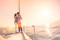Rich young couple in love on sailboat cheering at sunset Royalty Free Stock Photo
