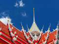 Richly crafted roof featuring garuda at thai temple gorgeously also called locally krut soaring into blue sky buddhist in capital Stock Photo