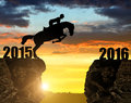 The rider on the horse jumping into the new year at sunset Royalty Free Stock Photo