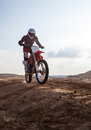 Rider performs stunts on a motorcycle in the desert Royalty Free Stock Photo