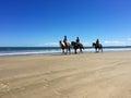Riders on horseback on 90 Mile Beach, Ahipara, New Zealand