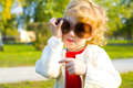 Ridiculous little girl puts on big sunglasses portrait of a playing in outdoors Stock Photo