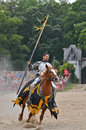 Riding knight a in armor rides horesback across a tournament field while carrying a standard Stock Image