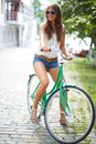 Riding in park portrait of a pretty woman on bicycle the Stock Photography