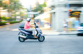 Riding a scooter panning shot of man in italy Stock Image