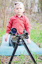 Rifle barrel and child selective focus to the of large hunting mounted on a tripod with small boy kneeling behind on mat wooded Stock Photography