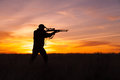 Rifle hunter shooting in sunset a silhoutted against a dramatic with shouldered Royalty Free Stock Image