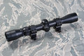 Rifle scope on camouflaged background Stock Images