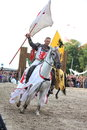 Riga latvia august member of the devils horsemen stunt te team riding horse and holding flag during festival on in Stock Photo