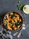 Rigatoni pasta with chickpeas, spinach and olives in a tomato sauce on a dark background, top view. Royalty Free Stock Photo