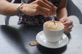 Right hand stir white freshly brewed Cappuccino coffee Royalty Free Stock Photo