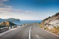 Right turn of mountain highway with blue sky and sea on a background Royalty Free Stock Image