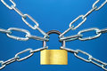 Rigid control padlock and chain on blue background Royalty Free Stock Image
