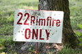 Rimfire sign with bullet holes a riddled in the shade of a large tree at an outdoor firing range Stock Photo