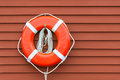 Ring buoy on red wooden wall hanging against background copy space Stock Photography