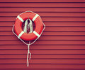 Ring buoy on red wooden wall hanging against background copy space vintage filter effects Royalty Free Stock Images
