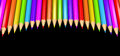Ring of rainbow colored pencils creating a circle shape isolated over black background. Royalty Free Stock Photo