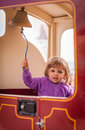 Ringing a train bell little girl small in the toy in an amusement park in brighton uk Stock Image