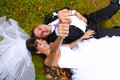 Rings up newly married couple laying on grass and showing hands with Royalty Free Stock Photography