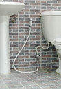 Rinsing spray or bidet on the brick wall background Royalty Free Stock Photography