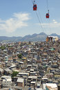 Rio de janeiro favela slum with red cable cars traveling in blue sky above complexo alemao Royalty Free Stock Photography
