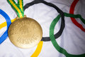 Rio olympics gold medal on flag de janeiro brazil february large commemorating the olympic games sits olympic background Royalty Free Stock Photo