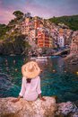 Riomaggiore Cinque Terre Italy , colorful village harbor front by the ocean, young woman watching sunset Royalty Free Stock Photo