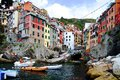 Riomaggiore cliff boats and colored houses of in italy Stock Photos