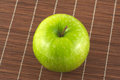 Ripe apple on brown wicker straw mat close up green Stock Photos