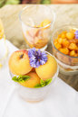 Ripe apricots in glass with blue flower and mint outdoor Royalty Free Stock Photos