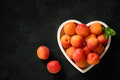 Ripe apricots on wooden white tray on black background. Royalty Free Stock Photo