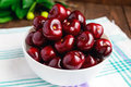 Ripe black cherries in a white bowl on a light background. Royalty Free Stock Photo