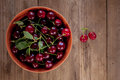 Ripe cherries with leaves in bowl on old wooden rustic backgroun organic background Stock Photo