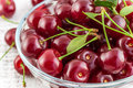 Ripe cherries with leaves in a bowl on a white background wooden Royalty Free Stock Image