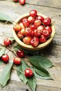 Ripe cherries with leaves on a wooden background, in a wooden pl