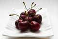Ripe cherries on white dish Stock Photos