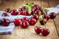 Ripe cherry on old wooden rustic background cherries with leaves an Royalty Free Stock Photos