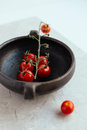 Ripe Cherry Tomatoes on Vine in Rustic Clay Pot Royalty Free Stock Photo