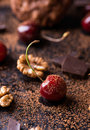 Ripe cherry walnuts and chocolate chunks cocoa powder on dark background selective focus Stock Photo