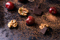 Ripe cherry walnuts and chocolate chunks cocoa powder on dark background selective focus Royalty Free Stock Image