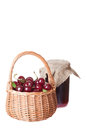 Ripe cherry in a wattled basket and bank of jam Stock Photos
