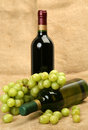 Ripe fruit and wine bottle of cluster of green grapes Royalty Free Stock Photography