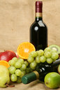 Ripe fruit and wine bottle of cluster of green grapes Stock Images
