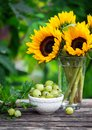 Ripe gooseberry fruits in white bowl with sunflower bouquet on wooden table, summer theme