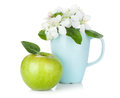 Ripe green apple and flowers in cup isolated on white background Stock Photos