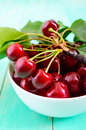 Ripe juicy red cherries in a ceramic bowl on a bright wooden background. Royalty Free Stock Photo