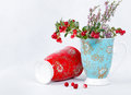 Ripe lingonberries and varicolored cups with ornament