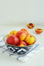 Ripe nectarines in oriental bowl full of on light background Royalty Free Stock Images