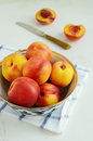 Ripe nectarines in oriental bowl full of on light background Stock Photo