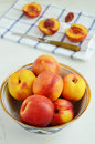 Ripe nectarines in oriental bowl full of on light background Royalty Free Stock Photos